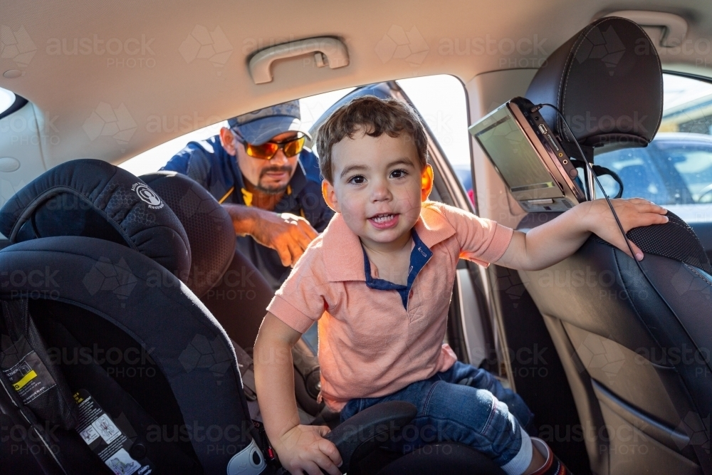 toddler in back seat of car with father leaning in the door - Australian Stock Image