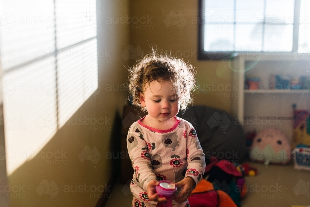 Toddler in sun flare playing with toys - Australian Stock Image