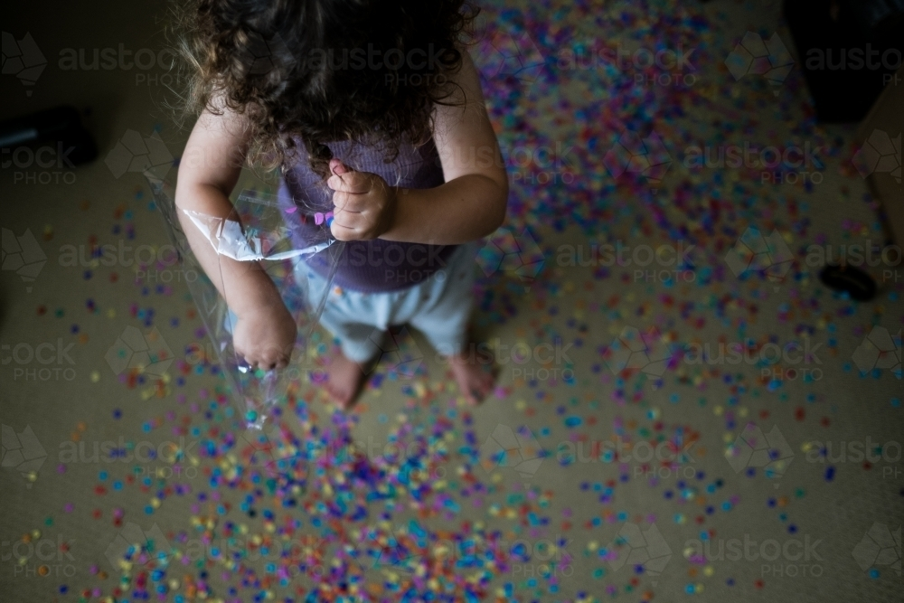 Toddler making mess with confetti - Australian Stock Image
