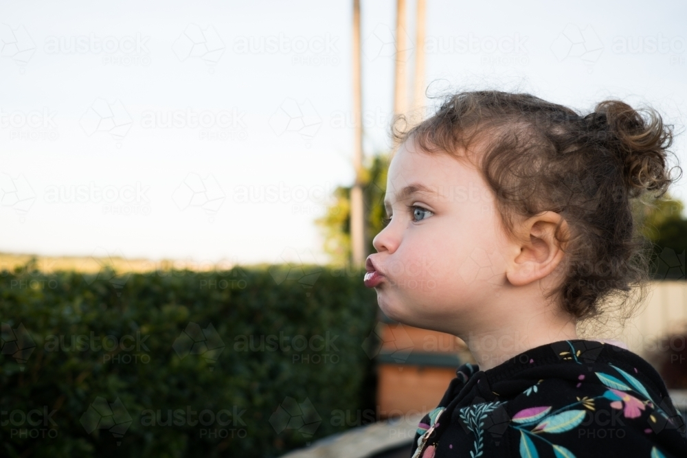 Toddler pulling a silly face outdoors - Australian Stock Image