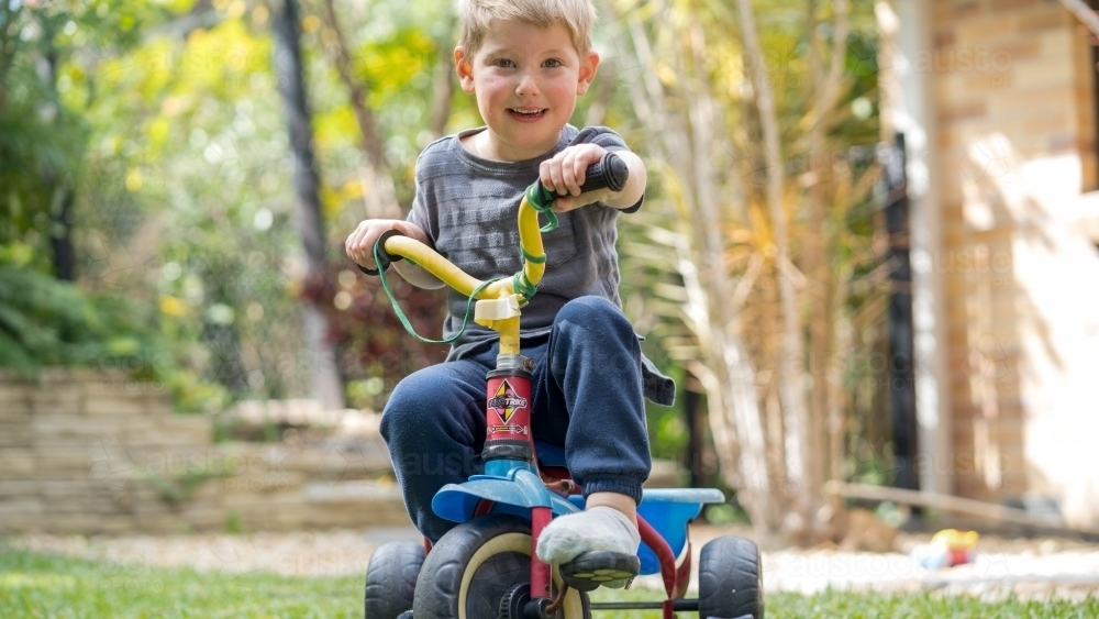Toddler riding tricycle in backyard - Australian Stock Image