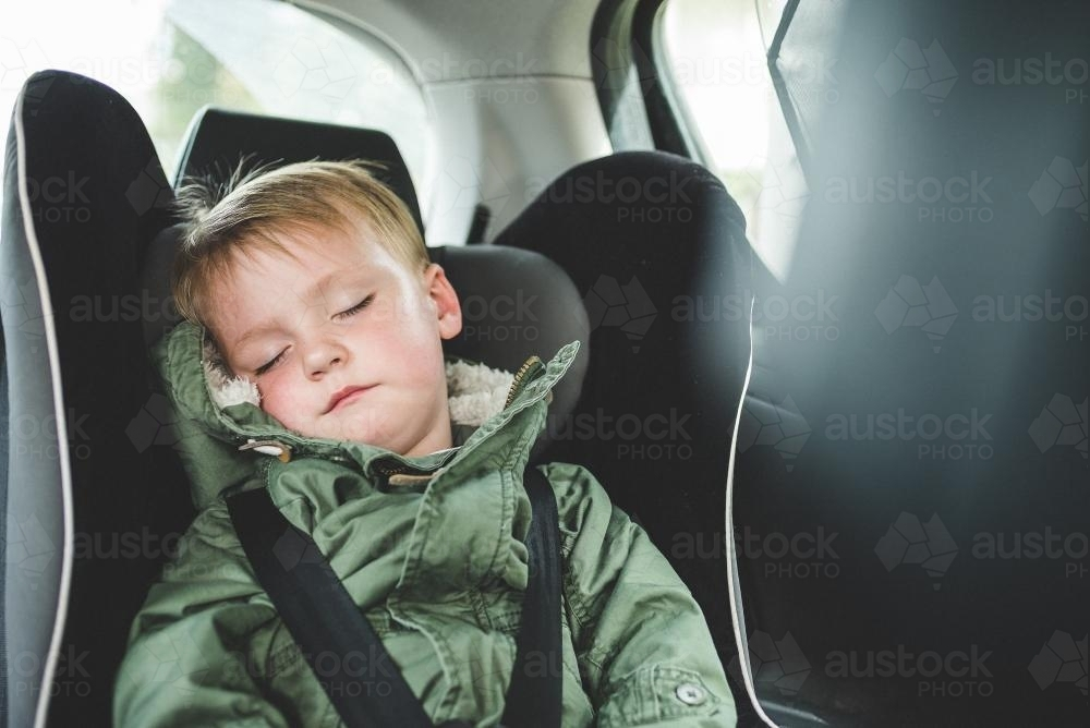 Toddler sleeping in car seat - Australian Stock Image