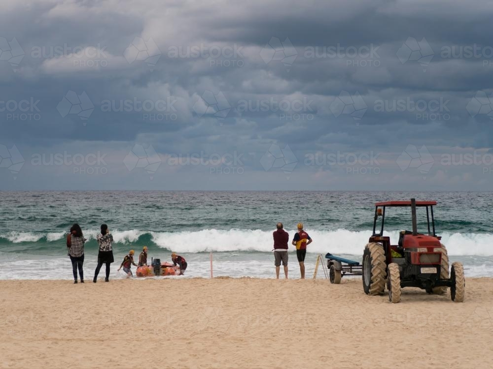 Tractor and trailer launching a boat into the surf while people watch - Australian Stock Image