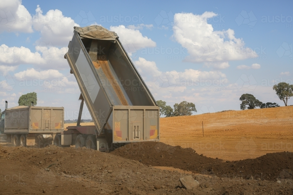 truck tipping soil on a construction site - Australian Stock Image