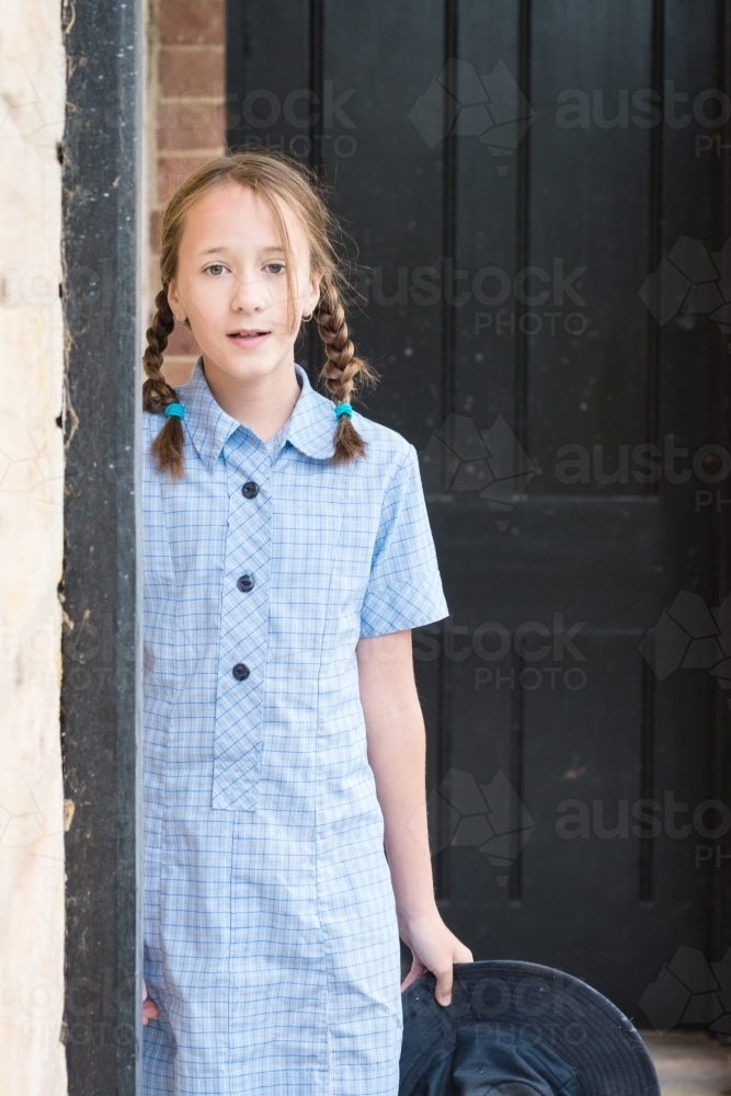 tween girl in blue primary school uniform dress - Australian Stock Image