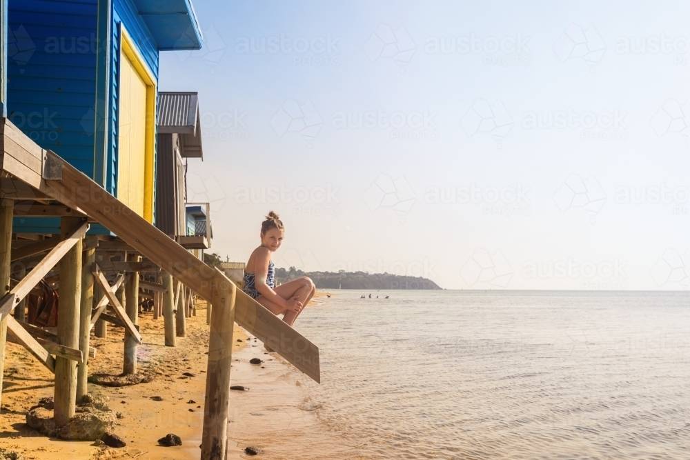 Tween girl sitting on stairs at a beach box, Mt Martha - Australian Stock Image