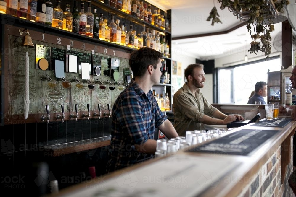 Two bartenders behind the bar at local craft beer bar - Australian Stock Image