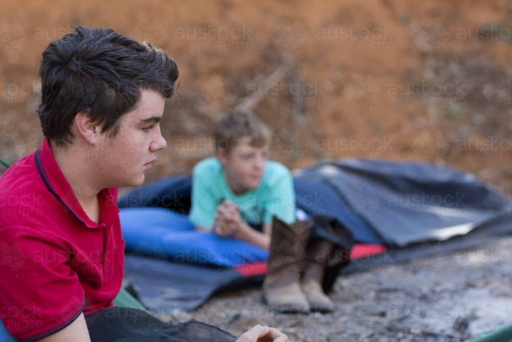 Two boys in swags camping out - Australian Stock Image