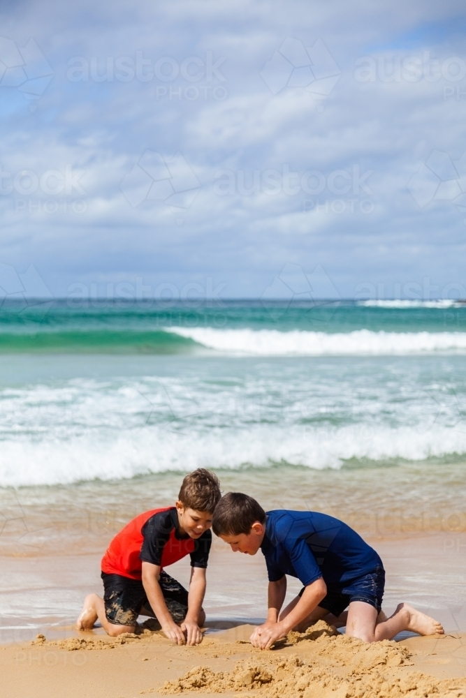 Two boys making sand castles and moats in the sand at the beach - Australian Stock Image