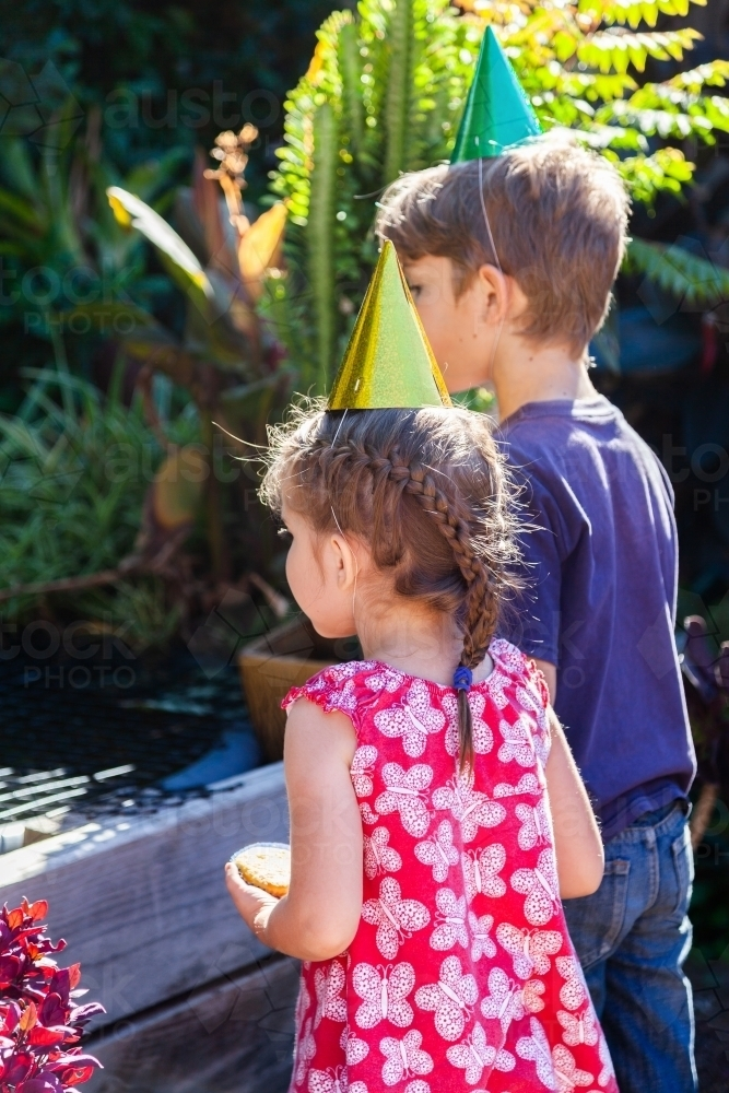 Two children looking at fish pond in garden - Australian Stock Image