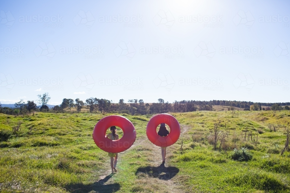 Two children walking on a track carrying inflatable rings - Australian Stock Image