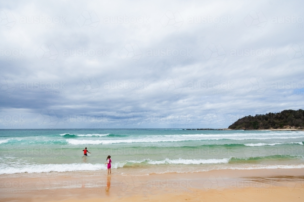 Two distant children playing in the beach waves  on overcast day - Australian Stock Image