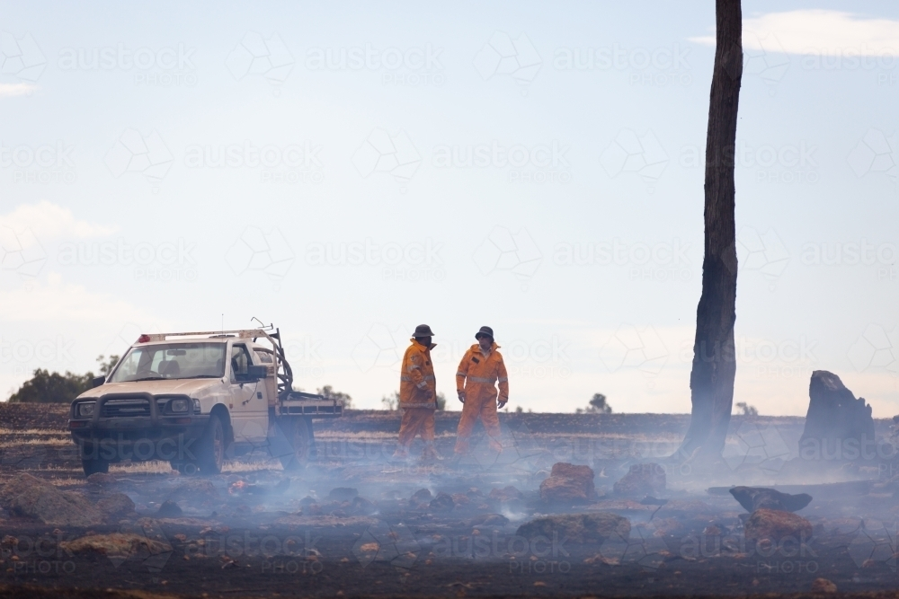 two fire service volunteers with vehicle in burnt out landscape with smoke - Australian Stock Image