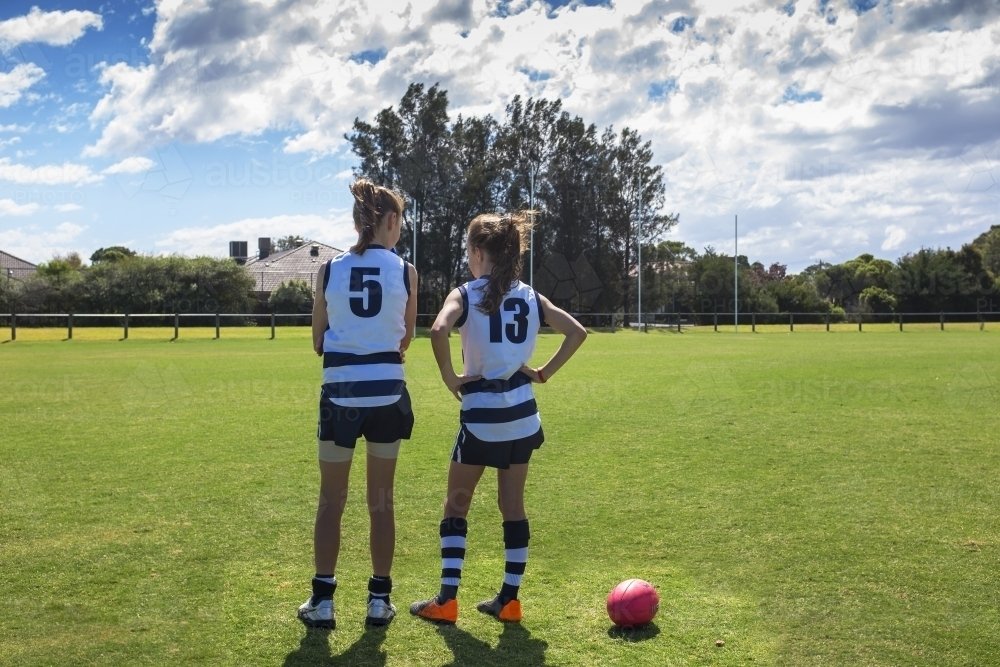 Two girl AFL players standing on the football ground - Australian Stock Image