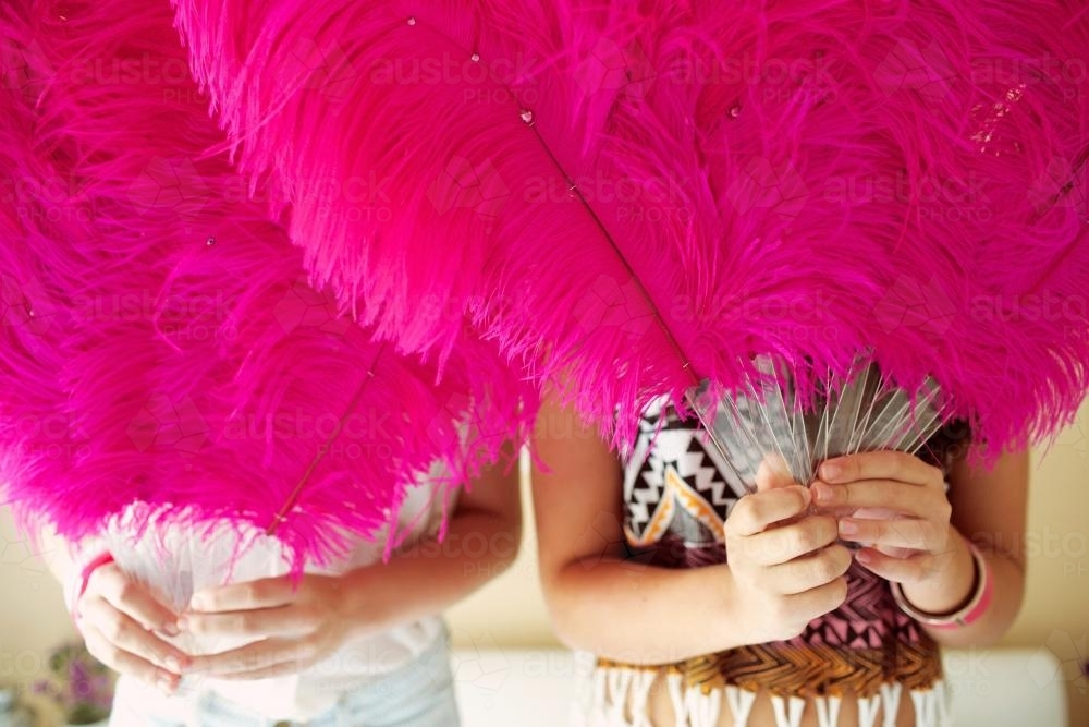 Two girls holding feather fans - Australian Stock Image