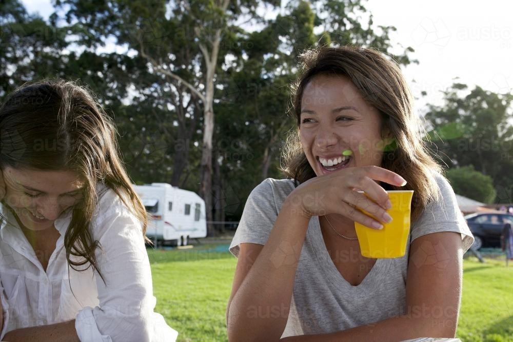 Two girls laughing sitting at a picnic table - Australian Stock Image