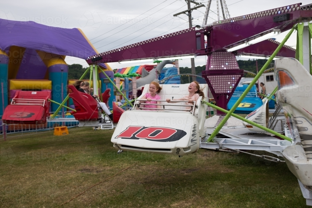 Two girls on an amusement ride at a country show - Australian Stock Image