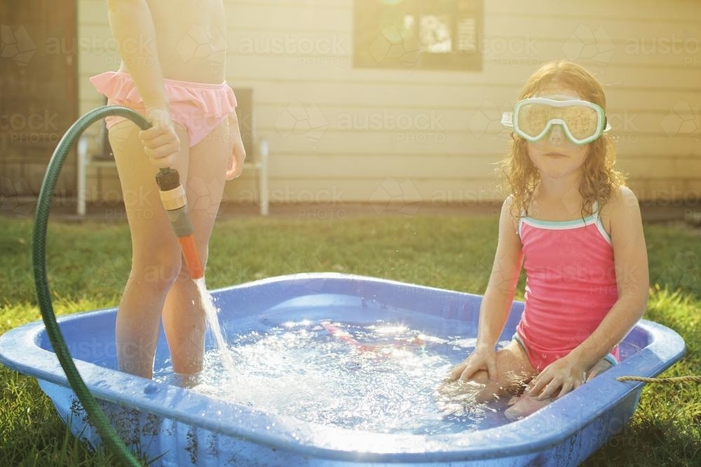 Two girls playing in a wading pool - Australian Stock Image