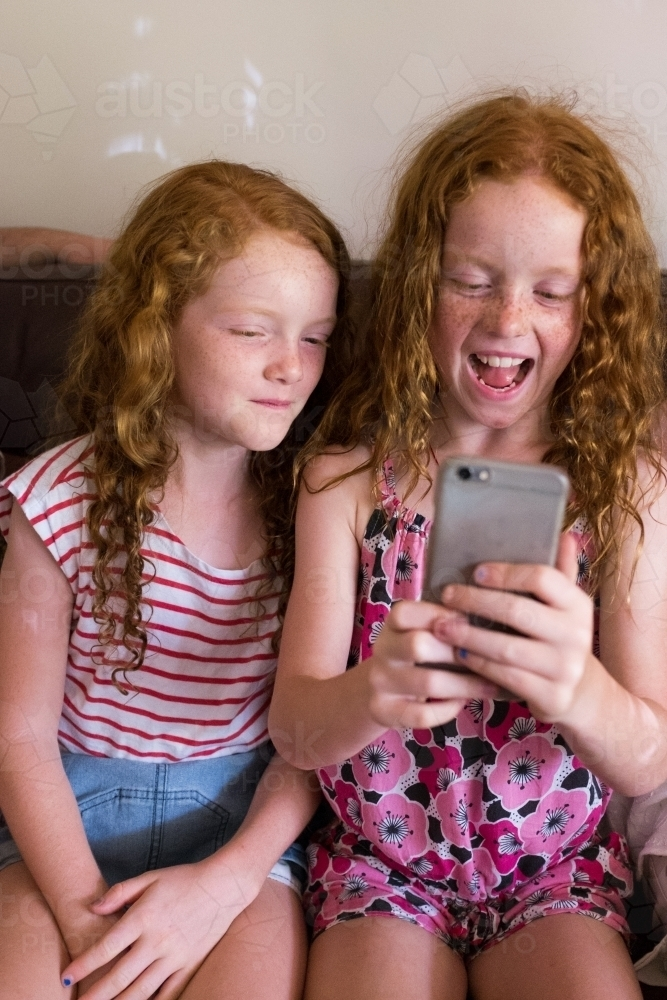 Two girls sitting on a couch playing on a smartphone - Australian Stock Image