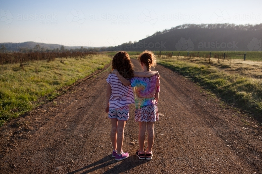 Two girls standing on a dirt road with arms around each other - Australian Stock Image
