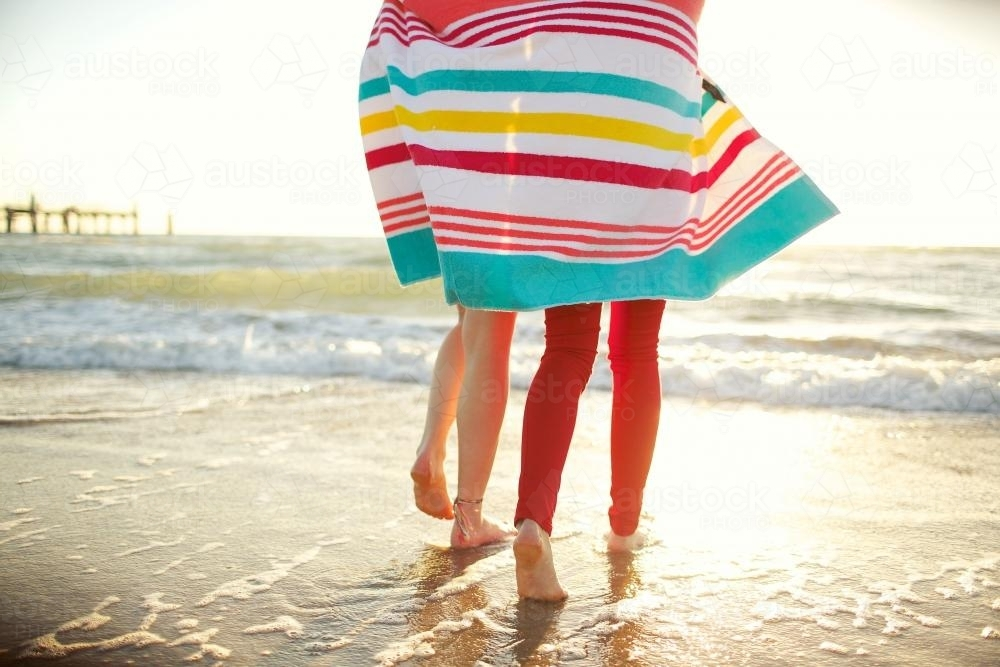 Two girls walking on the beach sharing a beach towel - Australian Stock Image