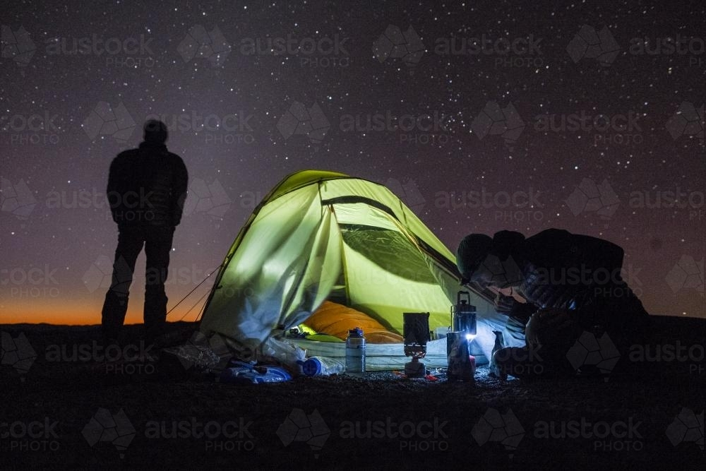 Two men silhouetted with tent camping under the stars - Australian Stock Image