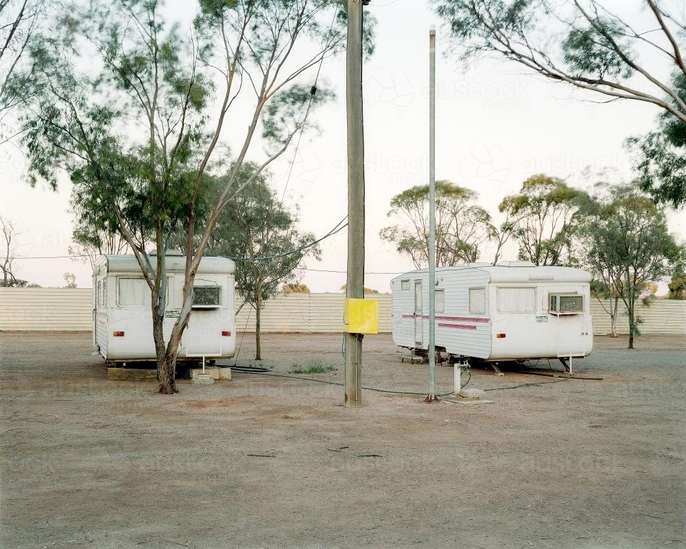 Two old caravans parked in dusty, remote caravan park - Australian Stock Image