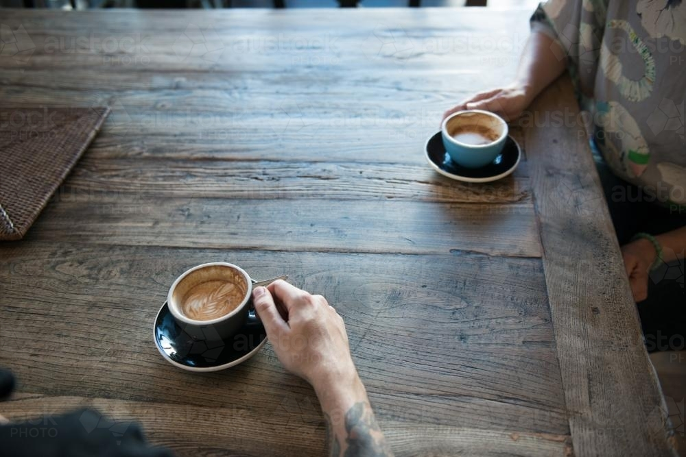Image of two people drinking coffee at a wooden table