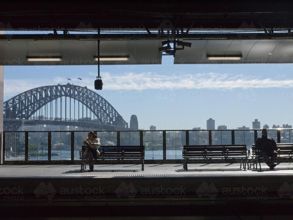Two people waiting at Circular Quay Railway Station with the Harbour Bridge in the background - Australian Stock Image