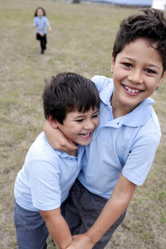 Two primary school boys in uniform playing outside - Australian Stock Image