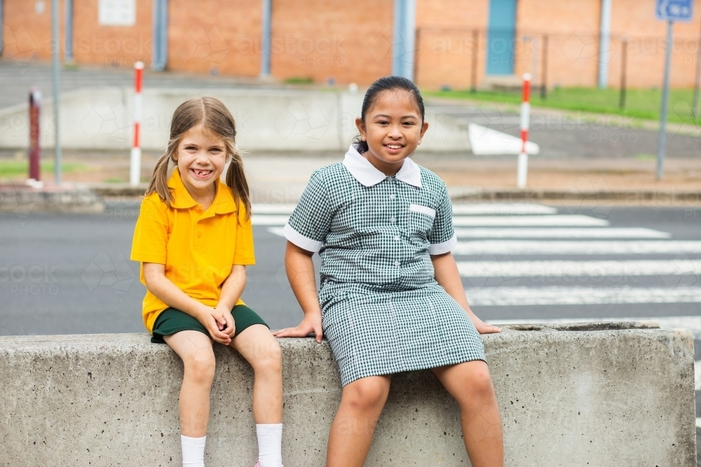 Two public school friends sitting together before school - Australian Stock Image
