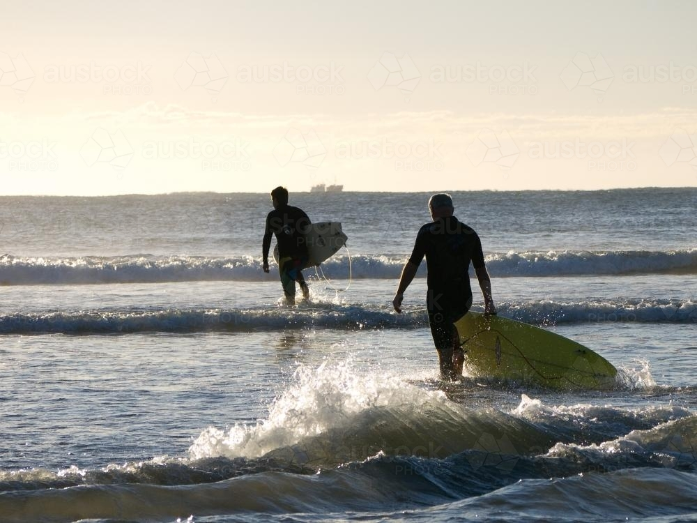 Two surfers entering the water in the early morning light - Australian Stock Image