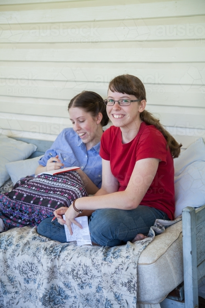 Two teen daughters talking together on the verandah - Australian Stock Image