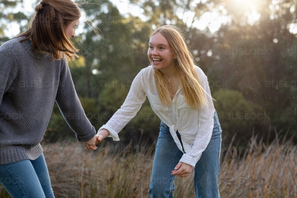 two teenage girls holding hands in natural setting - Australian Stock Image