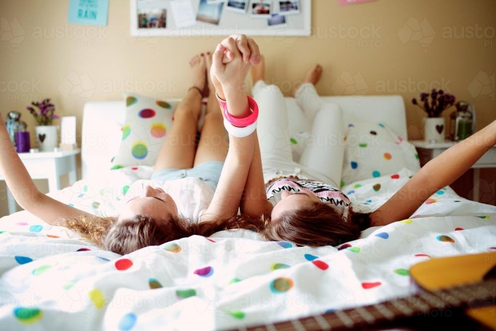 Two teenage girls lying on a bed holding hands - Australian Stock Image