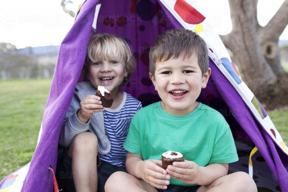 Two young boys eating cupcakes and smiling looking straight into the camera - Australian Stock Image