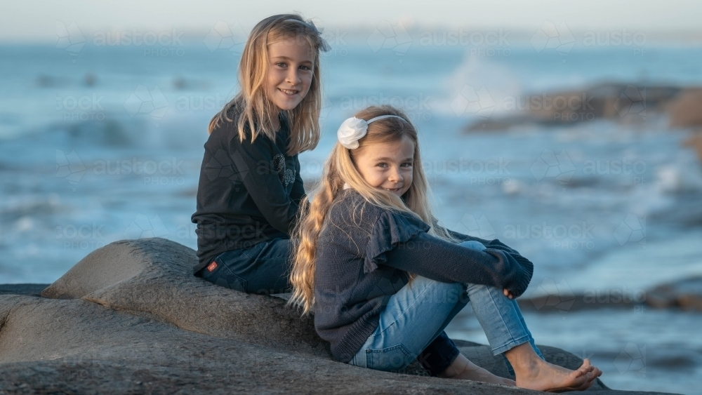 Two young girls sitting on rock at beach - Australian Stock Image