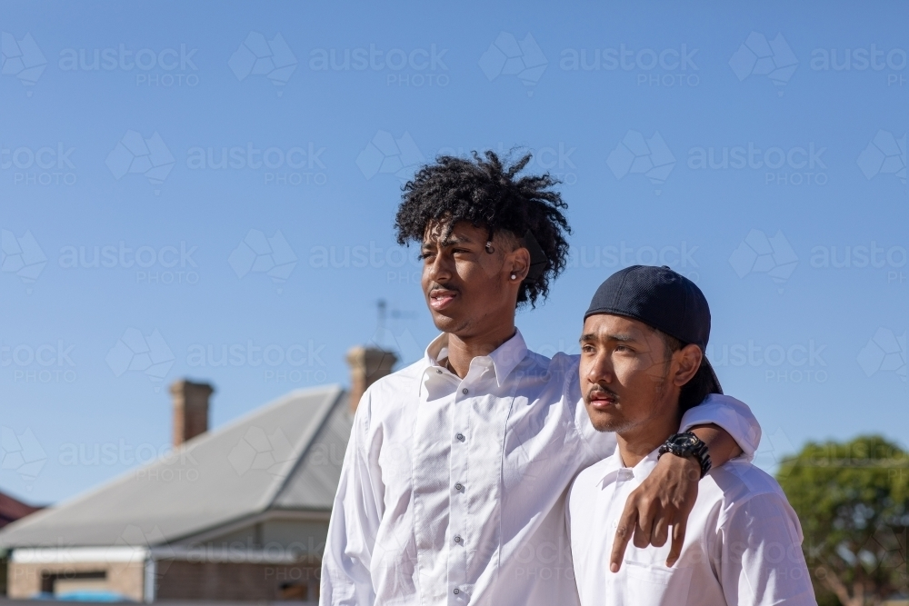 two young guys in white shirts - Australian Stock Image