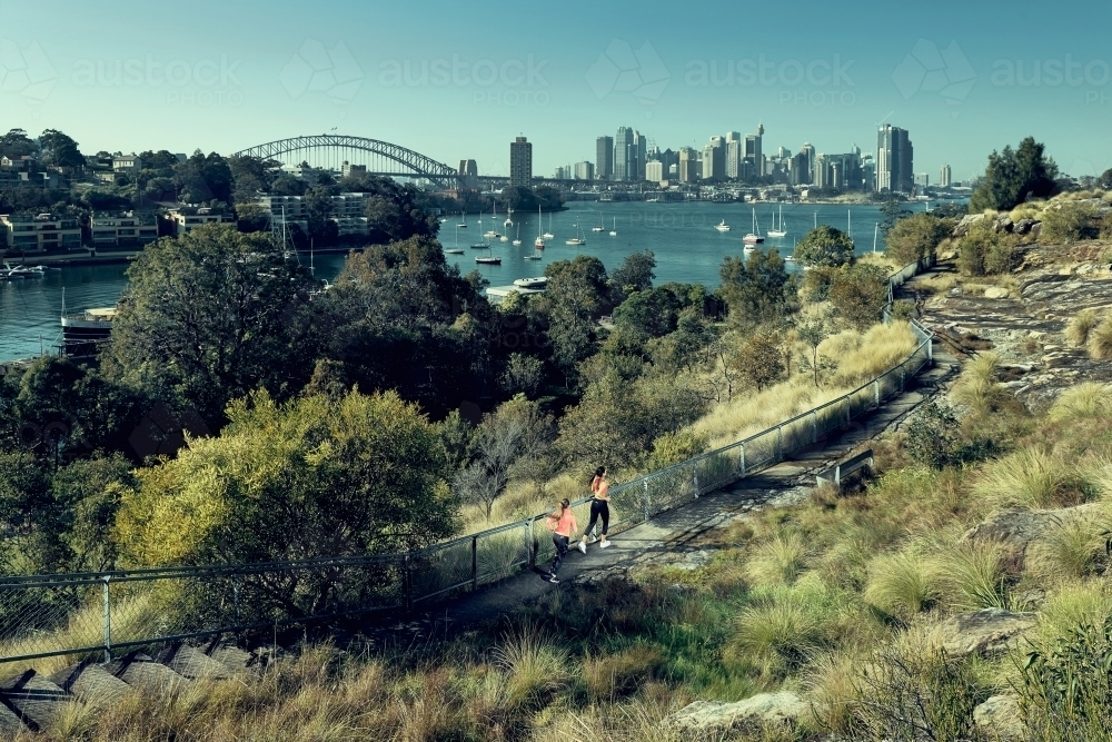 Two young people exercising against the sydney skyline - Australian Stock Image