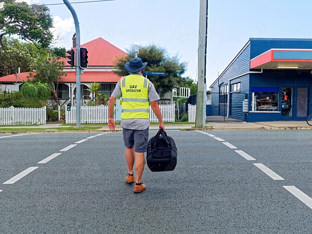 UAV Operator, man walking across the street with a drone in his bag - Australian Stock Image
