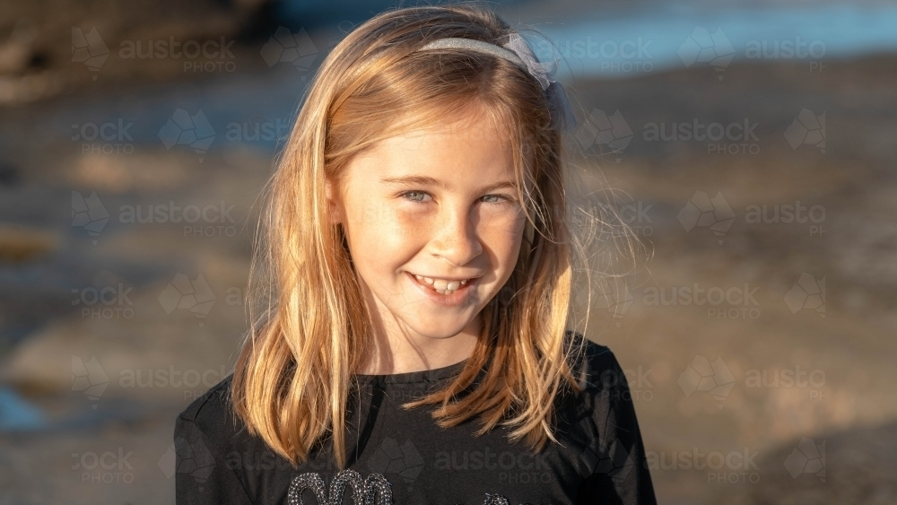 Under 10 girl smiling at camera at sunrise on beach - Australian Stock Image