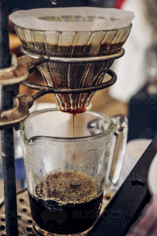 V60 filter coffee dripping into glass jug from right perspective - Australian Stock Image