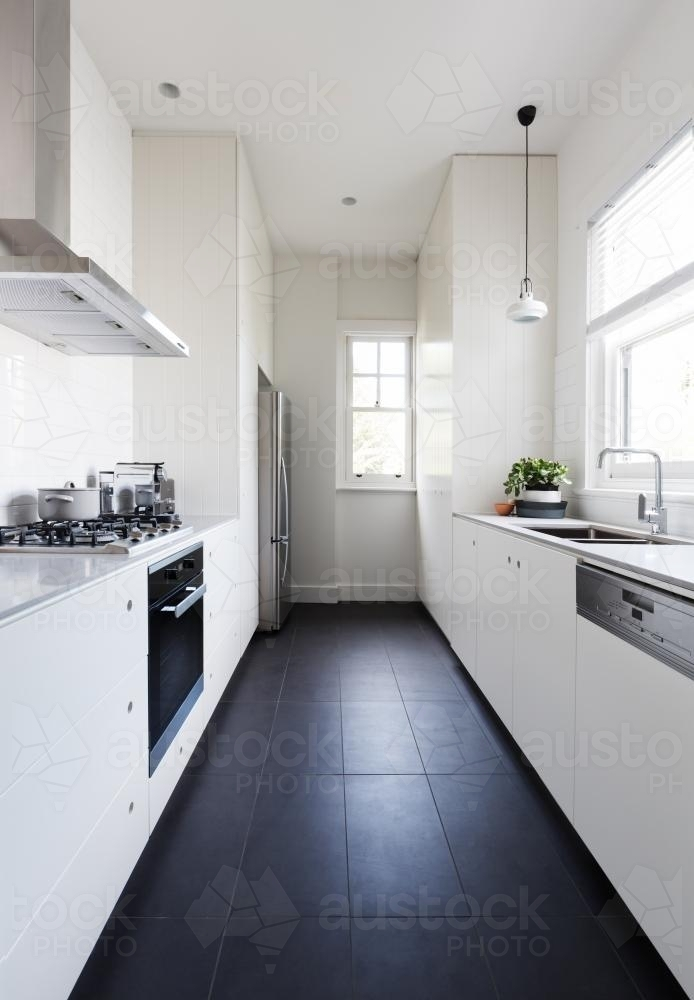 Vertical of a long galley style monochrome newly renovated kitchen - Australian Stock Image