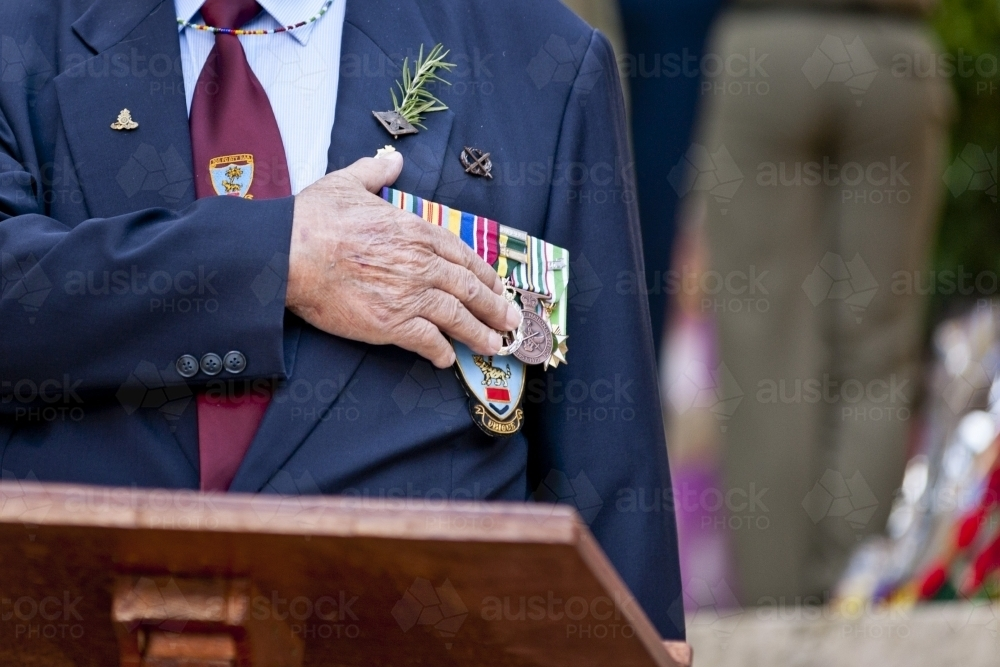 Veteran with his hand on his heart and medals during an Anzac service - Australian Stock Image