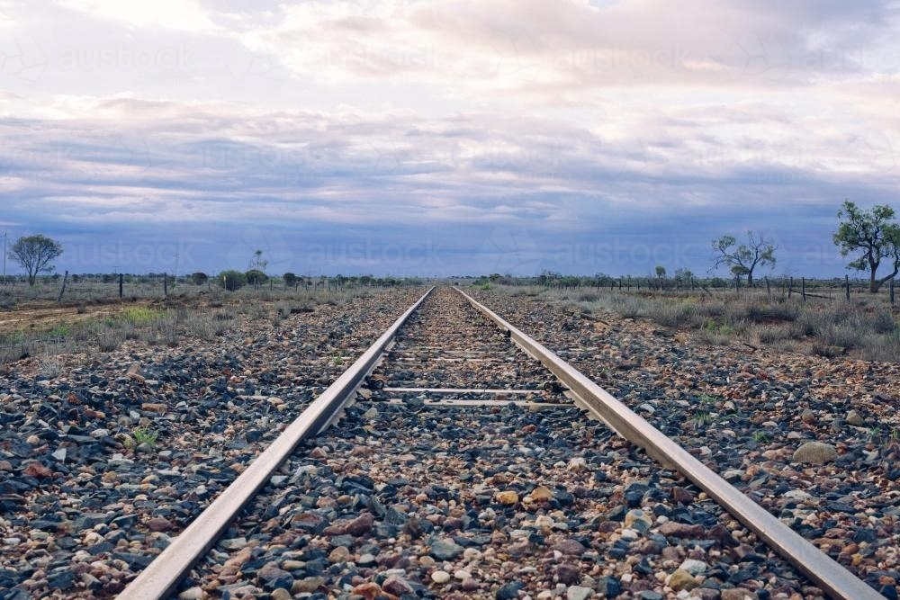 View down railway tracks into distance in remote location - Australian Stock Image
