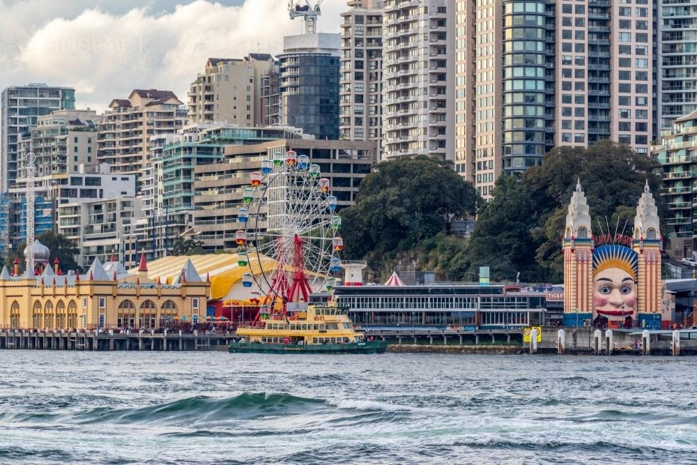 View of Luna Park and city skyscrapers across water - Australian Stock Image