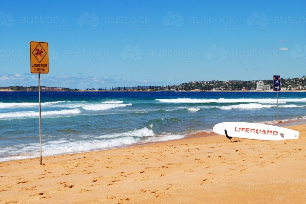 Warning sign and lifeguard surfboard on a beach in Sydney - Australian Stock Image
