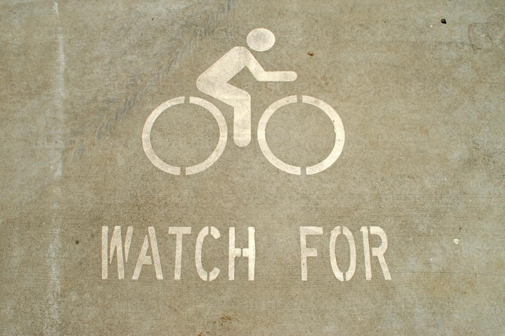 'Watch for bicycles' sign painted on the road