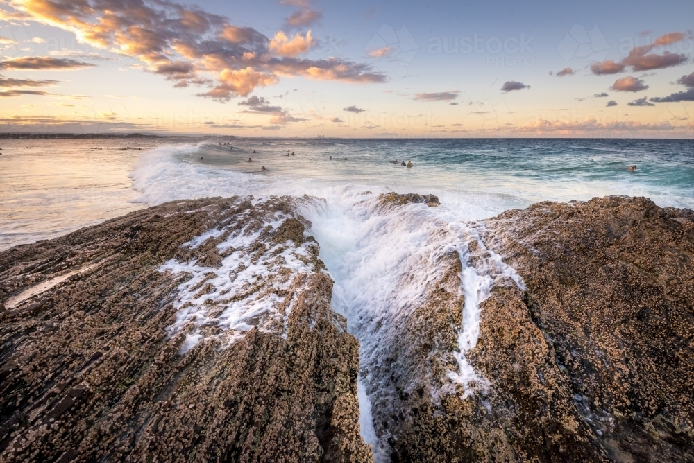 Waves breaking over rocks at the beach - Australian Stock Image