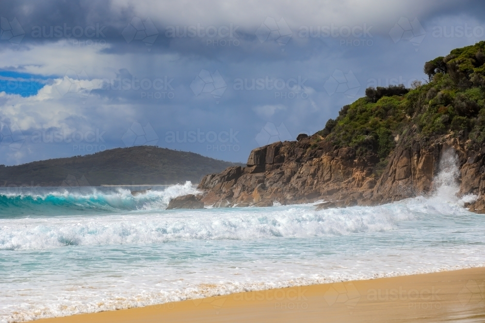 Waves crashing over rocky coastline against cloudy sky - Australian Stock Image